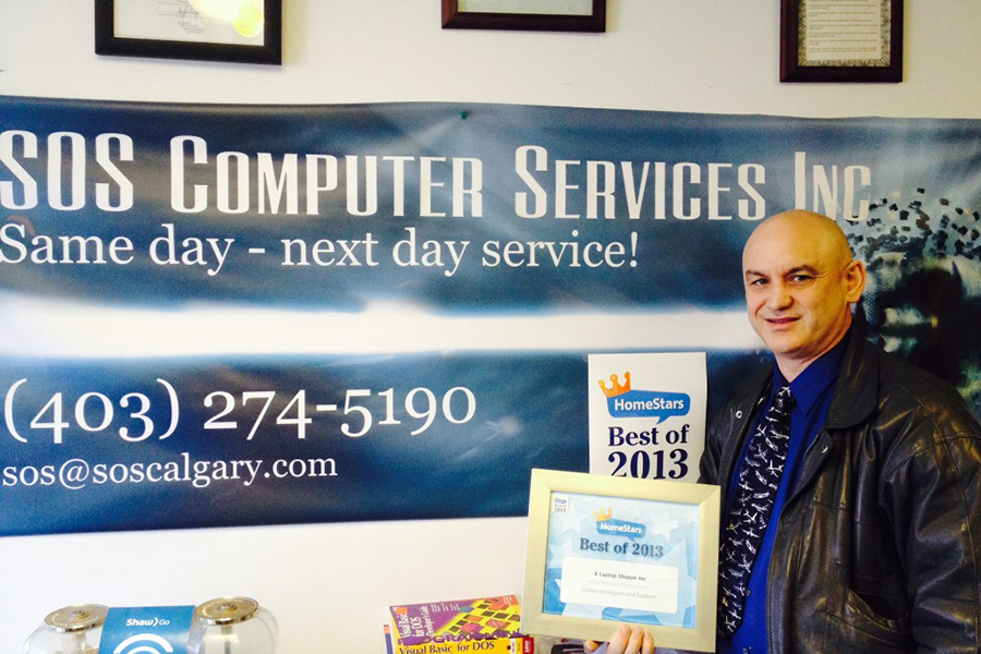 The store owner Mike, standing in front of a store banner and showcasing his 2013 award